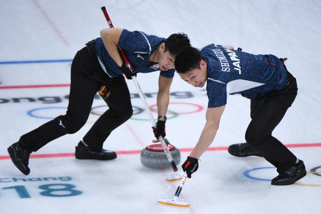 <p>Japan's Tetsuro Shimizu (R) brushes in front of the stone during the curling men's round robin session between Japan and Italy during the Pyeongchang 2018 Winter Olympic Games at the Gangneung Curling Centre in Gangneung on February 17, 2018 </p>