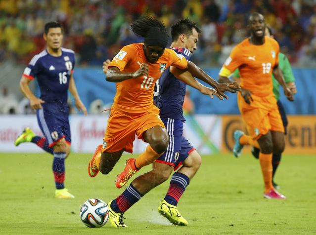 Ivory Coast's Gervinho (2nd L) fights for the ball with Japan's Shinji Okazaki (C) during their 2014 World Cup Group C soccer match at the Pernambuco arena in Recife, June 14, 2014. REUTERS/Stefano Rellandini (BRAZIL - Tags: SOCCER SPORT WORLD CUP)