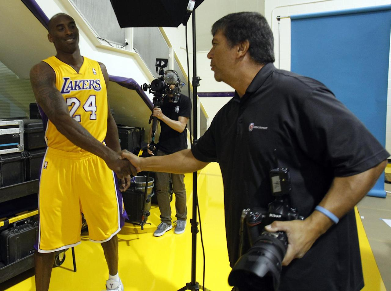 Los Angeles Lakers guard Kobe Bryant, left, shakes hands with NBA photographer Juan Ocampo during their NBA basketball media day at the team's headquarters on Saturday, Sept. 28, 2013, in El Segundo, Calif.  (AP Photo/Alex Gallardo)