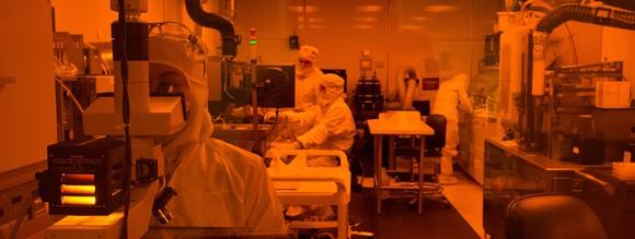 Lab in orange light with people wearing masks and sterile clothing working on various types of equipment.