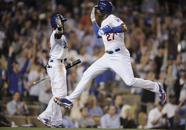 Los Angeles Dodgers' Matt Kemp, right, leaps while greeting Dee Gordon, left, after scoring on a sacrifice fly by Justin Turner during the seventh inning of a baseball game against the Detroit Tigers in Los Angeles, Tuesday, April 8, 2014. (AP Photo/Kelvin Kuo)