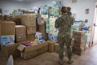 A soldier holds a child, one of the evacuees from Afghanistan in a storage facility with boxes of diapers at the Naval Station in Rota, southern Spain, Tuesday Aug. 31, 2021. The United States completed its withdrawal from Afghanistan late Monday, ending America's longest war. (AP Photo/ Marcos Moreno)