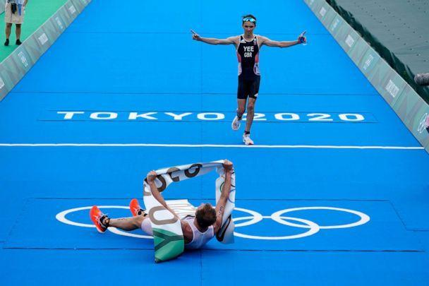 PHOTO: Kristian Blummenfelt of Norway celebrates his gold medal victory as Alex Yee of Great Britain crosses the finish line for the silver medal during the men's individual triathlon at the 2020 Summer Olympics, Monday, July 26, 2021, in Tokyo, Japan. (David Goldman/AP Photo)