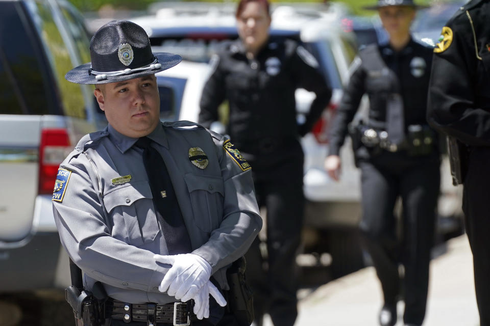 A police officer waits outside the Holmes Convocational Center for the funeral services of Watauga County Sheriff's Deputies Sgt. Chris Ward and K-9 Deputy Logan Fox in Boone, N.C., Thursday, May 6, 2021. The two deputies were killed in the line of duty. (AP Photo/Gerry Broome)