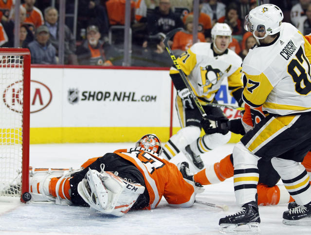 The puck bounces back out behind Philadelphia Flyers goalie Brian Elliott on a power-play goal by Pittsburgh Penguins' Evgeni Malkin (71) as Sidney Crosby, right, watches during the first period in Game 4 of an NHL first-round hockey playoff series Wednesday, April 18, 2018, in Philadelphia. (AP Photo/Tom Mihalek)