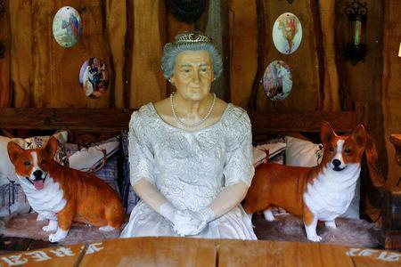"""A model of Queen Elizabeth and two mock-up corgis are pictured at """"Robin Hood's hut"""" at the British curiosities collection """"Little Britain"""" of Gary Blackburn, a 53-year-old tree surgeon from Lincolnshire, Britain, in Linz-Kretzhaus, south of Germany's former capital Bonn, Germany, August 24, 2017. Picture taken August 24, 2017. REUTERS/Wolfgang Rattay"""
