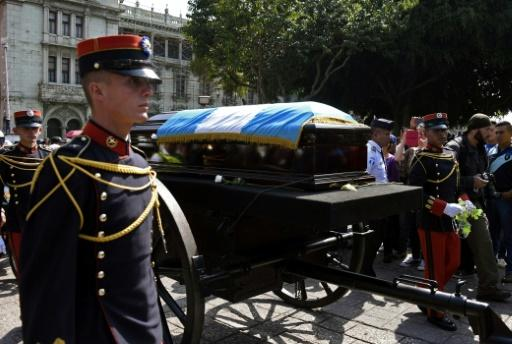 The brown wooden coffin carrying the remains of ex-president Alvaro Arzu, wrapped in the blue and white flag of Guatemala, was flanked by military officers as it made its way slowly from the National Palace of Culture to the Municipality building