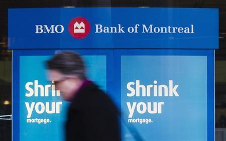 A man walks by a Bank of Montreal sign in Toronto