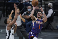 Phoenix Suns guard Devin Booker (1) shoots past San Antonio Spurs guard Devin Vassell (24) during the first half of an NBA basketball game in San Antonio, Saturday, May 15, 2021. (AP Photo/Eric Gay)