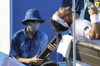 <p>Fabio Fognini of Italy receives cool air from a machine held by a ball boy during day one of the Tokyo 2020 Olympic Games at Ariake Tennis Park on July 24, 2021 in Tokyo, Japan. (Photo by Jean Catuffe/Getty Images)</p>