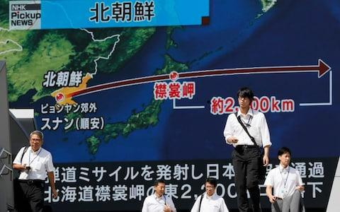 <span>Pedestrians walk under a large-scale monitor displaying the flying course of a North Korean ballistic missile flying over Japan </span> <span>Credit: EPA </span>