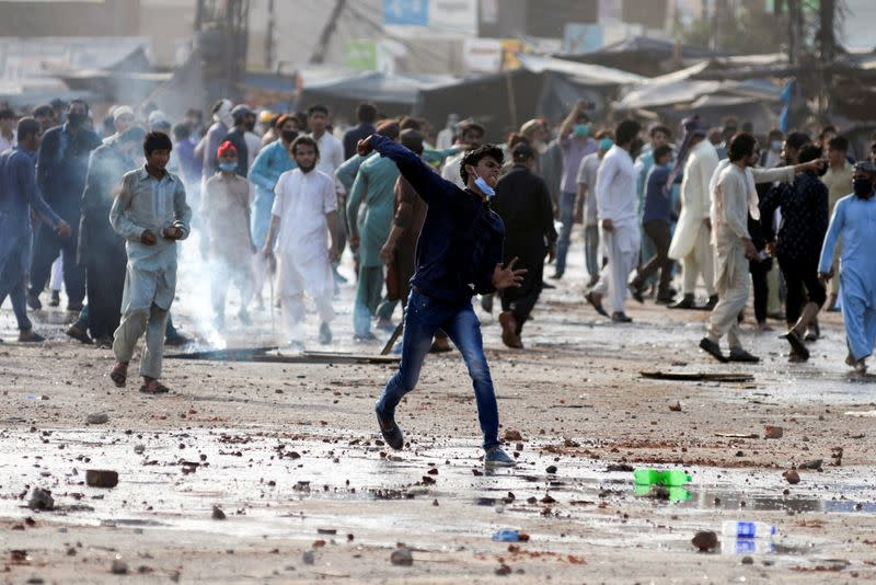 FILE PHOTO: A supporter of the Tehreek-e-Labaik Pakistan (TLP) Islamist political party hurls stones towards police (not in picture) during a protest against the arrest of their leader