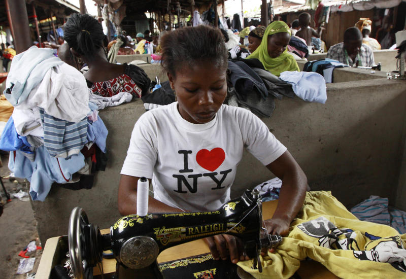 In this photo taken Monday, June. 18, 2012. A woman alters secondhand clothes at Katangua market in Lagos, Nigeria. Shipping container after shipping container arrives to this market in Lagos, Nigeria's largest city, filled to the brim with plastic-wrapped bales of secondhand clothes from the U.S. and elsewhere in the world. Traders scour, barter, hem and haw over T-shirts, bras, pants and shoes sent to help clothe a nation of more than 160 million people where the textile industry largely collapsed years ago.  (AP Photo/Sunday Alamba)