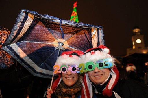 <p>A couple wearing 2013 glasses celebrates the beginning of New Year's Day under the rain at Puerta del Sol in Madrid on December 31, 2012. Uncowed by cold, rain and recession, revellers in Madrid on Monday sought to numb the pain of economic crisis with a glass of wine and plenty of cheer as the New Year reached Spain.</p>