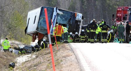Rescue workers are seen at the site where a bus carrying school children and adults rolled over on a road close to the town of Sveg