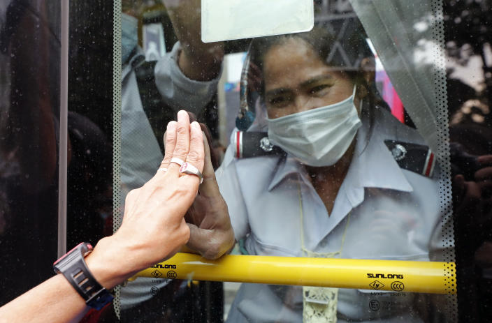 A pro-democracy protester, partly seen at left, and a bus ticket clerk, right, gesture three-fingered flash each other, in Bangkok, Thailand, Sunday, Oct. 25, 2020. Pro-democracy protesters in Thailand gathered again Sunday in Bangkok, seeking to keep up pressure on the government a day ahead of a special session of Parliament called to try to ease political tensions. (AP Photo/Sakchai Lalit)