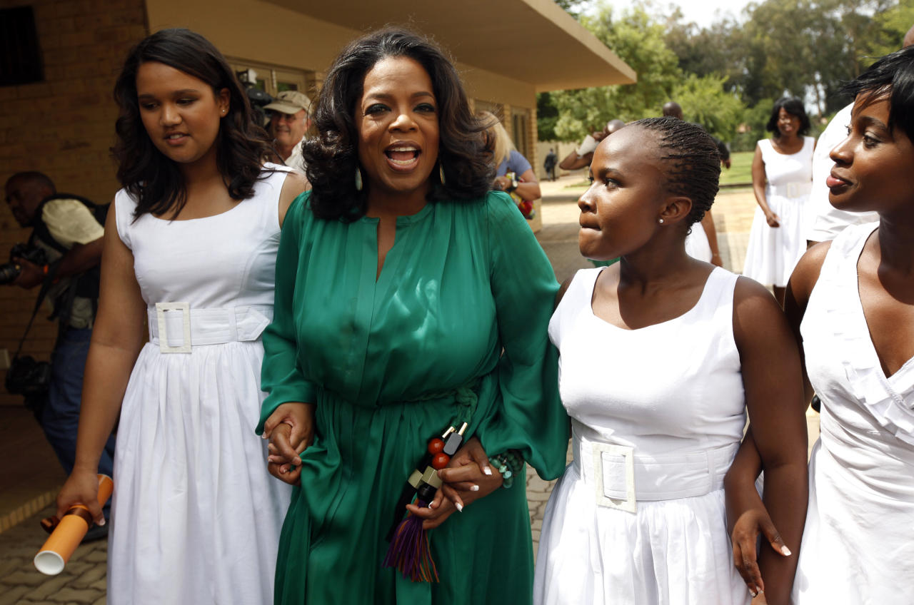 """Oprah Winfrey walks with honor graduates after the first graduation ceremony at Oprah Winfrey's leadership academy for girls in Henley on Klip, South Africa, Saturday Jan. 14, 2012. Winfrey said the first students to graduate from her academy for underprivileged South African girls were """"free to soar,"""" during a graduation speech Saturday.(AP Photo/Jerome Delay)"""