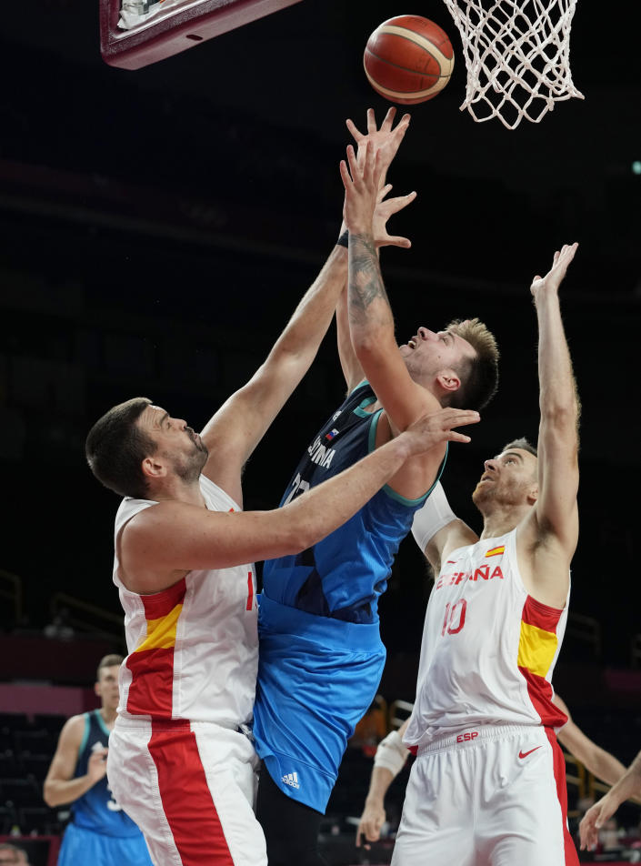 Slovenia's Luka Doncic (77) goes to the basket between Spain's Marc Gasol, left, and Victor Claver (10) during a men's basketball preliminary round game at the 2020 Summer Olympics, Sunday, Aug. 1, 2021, in Saitama, Japan. (AP Photo/Eric Gay)