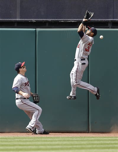 Minnesota Twins' Aaron Hicks, right, jumps but cannot get to a triple hit by Cleveland Indians' Jason Kipnis in the seventh inning of a baseball game, Saturday, May 4, 2013, in Cleveland. Twins' Josh Willingham backs up the play at left. (AP Photo/Tony Dejak)
