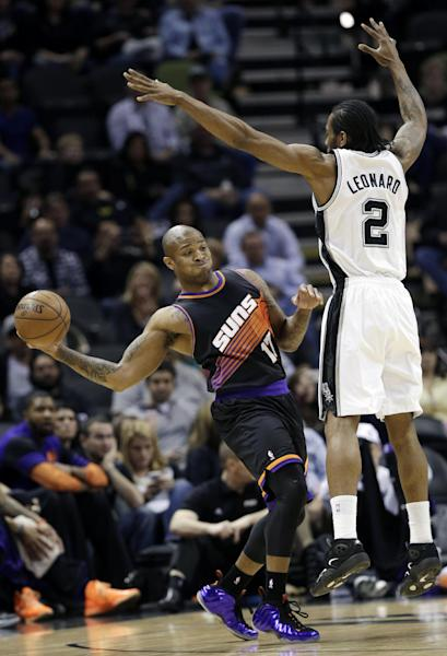 Phoenix Suns' P.J. Tucker (17) passes around San Antonio Spurs' Kawhi Leonard (2) during the first half of an NBA basketball game, Wednesday, Feb. 27, 2013, in San Antonio. (AP Photo/Eric Gay)