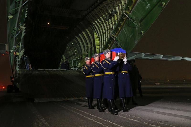 Russian honour guards carry the coffin of pilot Oleg Peshkov out of a plane at Chkalovsky military airport outside Moscow, on November 30, 2015