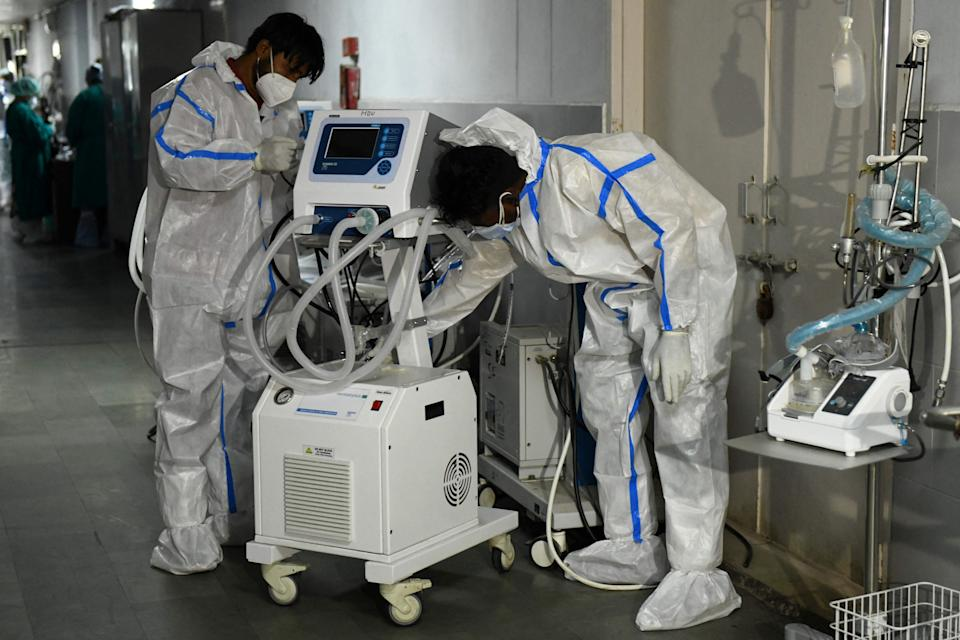 Health workers wearing protective gear place a defunct ventilator machine in the corridor of a hospital amid Covid-19 coronavirus pandemic in Amritsar (Narinder Nanu/AFP via Getty Images)