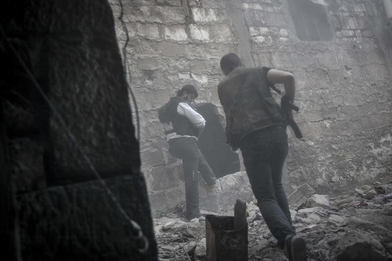In this Saturday, Nov. 03, 2012 photo, rebel fighters run for cover through smoke from an explosion as they try to repel a coordinated attack using mortar, tank and aerial artillery fire by loyalists to President Bashar Assad in the Jedida district of Aleppo, Syria. (AP Photo/Narciso Contreras)