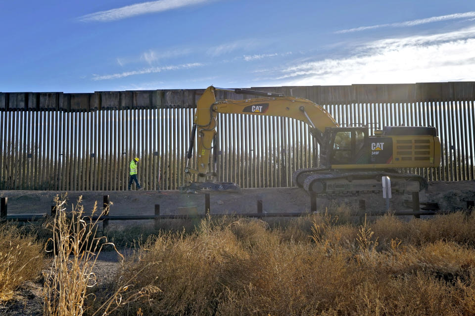 The old border fence, below grade, which allowed animal migration into Mexico, remains in place as a construction worker walks along a section of new border wall in San Bernardino National Wildlife Refuge, Tuesday, Dec. 8, 2020, in Douglas, Ariz. Construction of the border wall, mostly in government owned wildlife refuges and Indigenous territory, has led to environmental damage and the scarring of unique desert and mountain landscapes that conservationists fear could be irreversible. (AP Photo/Matt York)