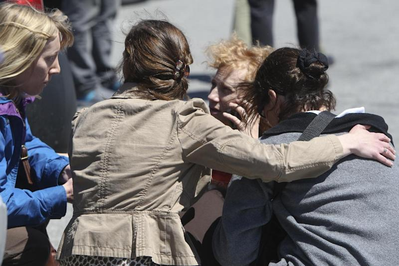 People gather in the parking lot outside New River Valley Mall in Christiansburg, Va. on Friday, April 12, 2013. Officials say two women have been shot at the community college section of the mall and a suspect is in custody. (AP Photo/The Roanoke Times, Daniel Lin)