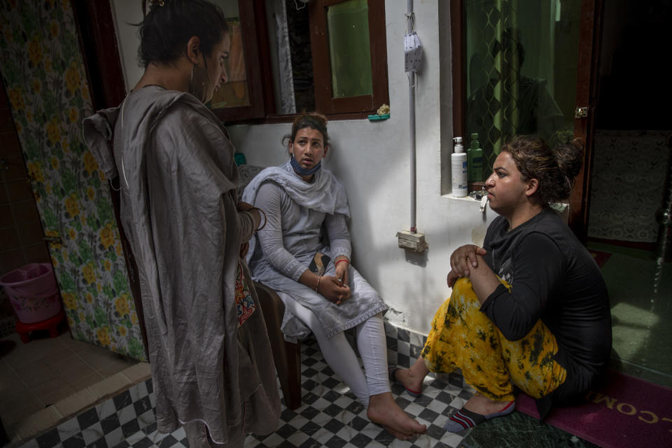 Transgender Kashmiris Azimi Bhat, right, Hinna Bhat, center and Khushi Mir converse outside their guru's house at the end of a special meet of their community members in Srinagar, Indian controlled Kashmir, Thursday, June 3, 2021. Mir, along with four young boys, has created a volunteer group distributing food kits to transgender community members. (AP Photo/ Dar Yasin)