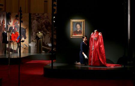 A member of the Royal Collection Trust poses for photographers next to Britain's Queen Elizabeth's 'Mantle of The Order of The British Empire' robe, ahead of the opening of an exhibition entitled 'Fashioning a Reign: 90 Years of Style from the Queen's Wardrobe', at Buckingham Palace, in London, Britain July 21, 2016. REUTERS/Peter Nicholls
