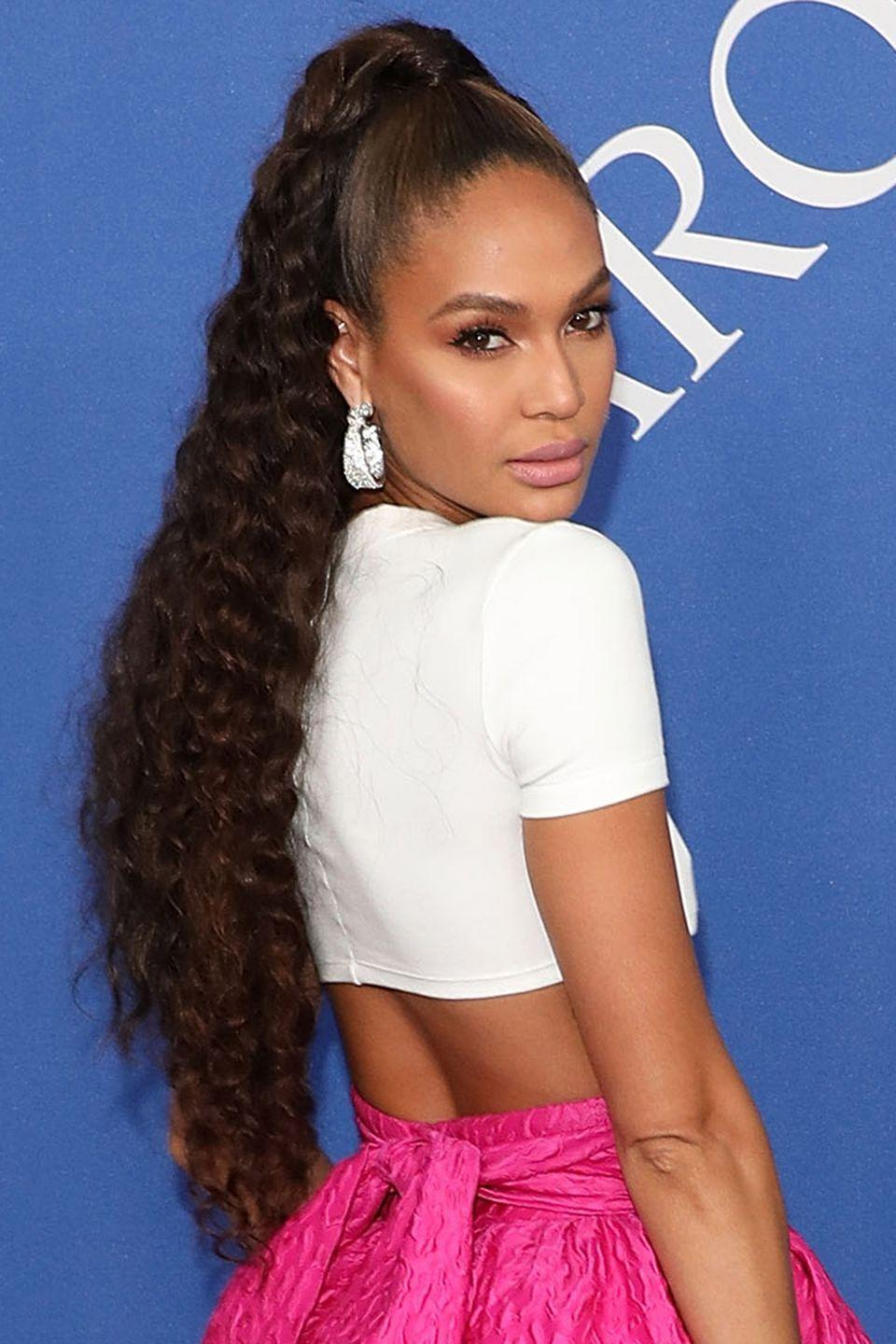<p>Take note of Joan Small's ponytail – by enhancing the natural texture of your hair, either by brushing out your own curls or using a crimping tool, you'll hair will look so much thicker.</p>