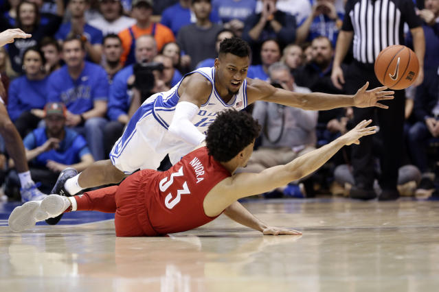 Duke forward Javin DeLaurier and Louisville forward Jordan Nwora (33) go to the floor while chasing the ball during the second half of an NCAA college basketball game in Durham, N.C., Saturday, Jan. 18, 2020. Louisville won 79-73. (AP Photo/Gerry Broome)