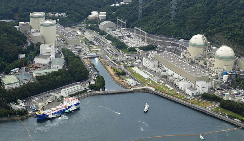A freighter, left in foreground, carrying MOX, a mixture of uranium and plutonium oxide, arrives at the Takahama nuclear power station in Takahama town, Fukui prefecture, Japan, Thursday, June 27, 2013. The power plant on the Sea of Japan coast has received the first shipment of reprocessed nuclear reactor fuel sent from France since the 2011 disaster that forced it to shut down reactors. Operators of the plant are hoping to use the fuel once they get the go-ahead to restart their reactors. (AP Photo/Kyodo News) JAPAN OUT, MANDATORY CREDIT
