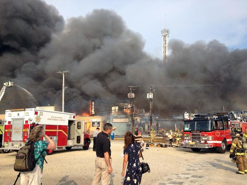 Firefighters battle a raging fire on the boardwalk in Seaside Heights, N.J. that apparently started in an ice cream shop and has spread several blocks down, Thursday, Sept. 12, 2013. The boardwalk was damaged in Superstorm Sandy and was being repaired. (AP Photo/The Asbury Park Press, Erik Larsen) MANDATORY CREDIT: PAPER AND PHOTOGRAPHER; NO SALES