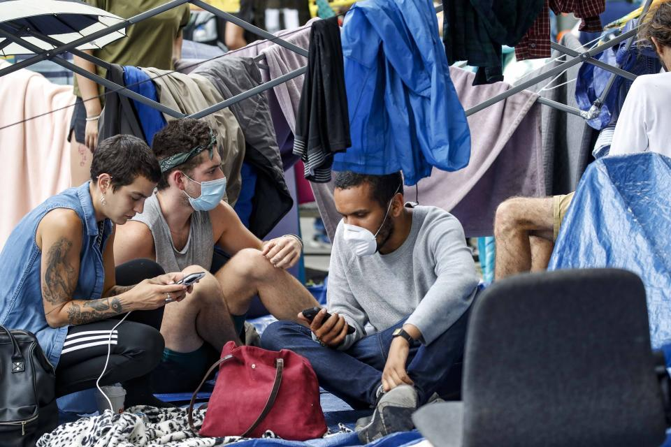 Protesters gather at an encampment outside City Hall, Tuesday, June 30, 2020, in New York. City Council members were due to debate and vote Tuesday night on a plan to shift $1 billion from policing to education and social services, with time running short ahead of the fiscal year that begins Wednesday. (AP Photo/John Minchillo)
