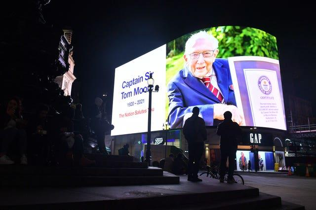 Members of the public stand in front of a tribute to Captain Sir Tom Moore at the Piccadilly Circus lights, central London, as they join in with a nationwide clap in honour of the 100-year-old charity fundraiser who died on Tuesday after testing positive for Covid-19