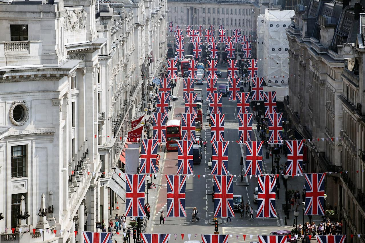 LONDON, ENGLAND - MAY 22:  Members of the public walk below Union flags flying above Regent Street on May 22, 2012 in London, England. The flags are part of the celebration of the forthcoming Diamond Jubilee of Her Majesty Queen Elizabeth II.  (Photo by Dan Kitwood/Getty Images)