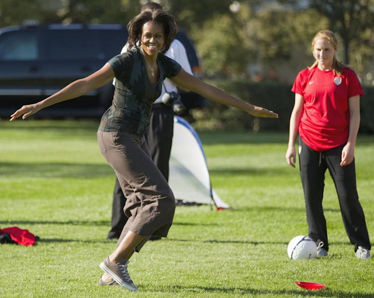 FILE - In this Oct. 6, 2011, file photo, first lady Michelle Obama plays soccer on the South Lawn of the White House in Washington, as part of a Let's Move! clinic. The nation's first lady turns 50 on Friday and, by her own account, feels more relaxed now that President Barack Obama's days as a candidate for elected office are over. (AP Photo/Evan Vucci)