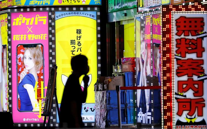A man wears a mask while walking through the Kabukicho district in Tokyo - REUTERS/Kim Kyung-Hoon