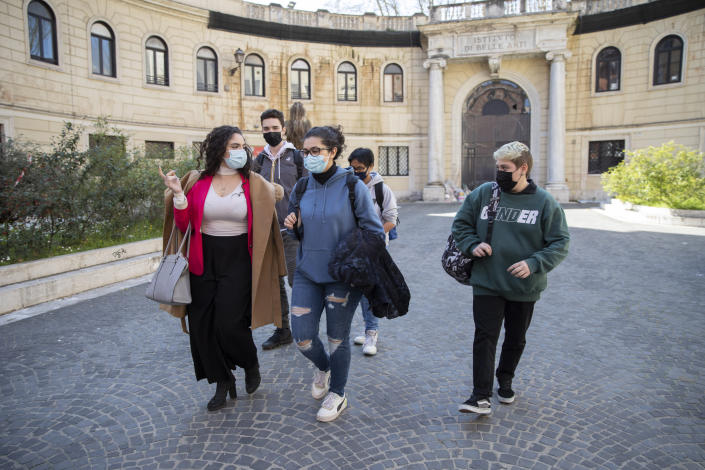 Matteo Coccimiglio, right, leaves the Ripetta art school in Rome, Wednesday, March 24, 2021. Matteo is an 18-year-old student who identifies as a man and is in the process of changing his legal gender from female to male. The Ripetta school of art in Rome - where he studies - recently joined a handful of high schools in Italy that give transgender students the right to be known by a name other than the one they were given at birth. The initiative is meant to create an environment where transgender students feel secure and reflects a growing awareness in Italy of gender dysphoria among teenagers and children. (AP Photo/Alessandra Tarantino)