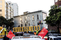 A truck pulls a Victorian home through San Francisco on Sunday, Feb. 21, 2021. The house, built in 1882, was moved to a new location about six blocks away to make room for a condominium development. According to the consultant overseeing the project, the move cost approximately $200,000 and involved removing street lights, parking meters, and utility lines. (AP Photo/Noah Berger)