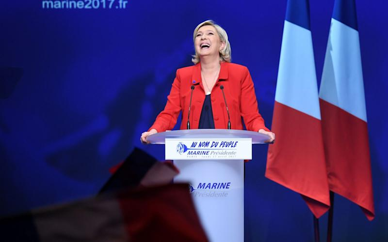 French presidential election candidate for the far-right Front National (FN) party Marine Le Pen reacts on stage during a campaign meeting in Paris  - Credit: ALAIN JOCARD/AFP
