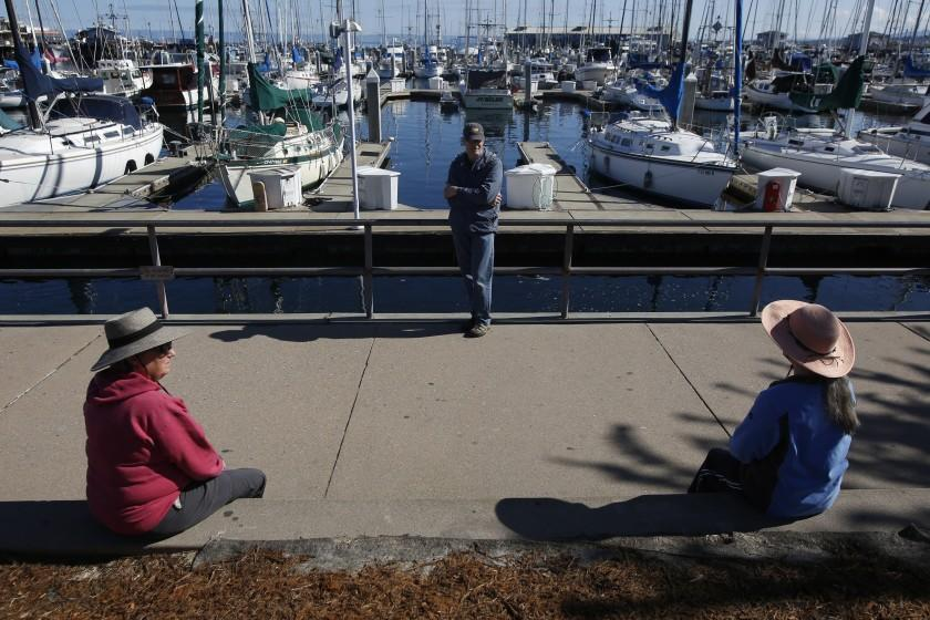 In this photo taken Tuesday April 7, 2020, area residents Terry Hanna, left, her husband, Mike, center, and Melanie Cervi, right, practice social distancing near Fisherman's Wharf in Monterey, Calif., Tuesday, April 7, 2020.