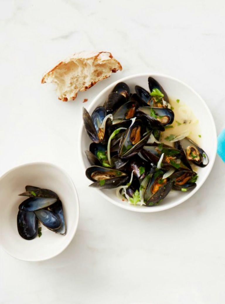 """<p>Mussels may feel luxurious, but in reality, they're actually pretty easy to make. Throw some fries in the oven for a classic moules frites. </p><p><em><a href=""""https://www.womansday.com/food-recipes/food-drinks/recipes/a53285/white-wine-mussels/"""" rel=""""nofollow noopener"""" target=""""_blank"""" data-ylk=""""slk:Get the White Whine Mussels recipe."""" class=""""link rapid-noclick-resp"""">Get the White Whine Mussels recipe.</a></em></p>"""