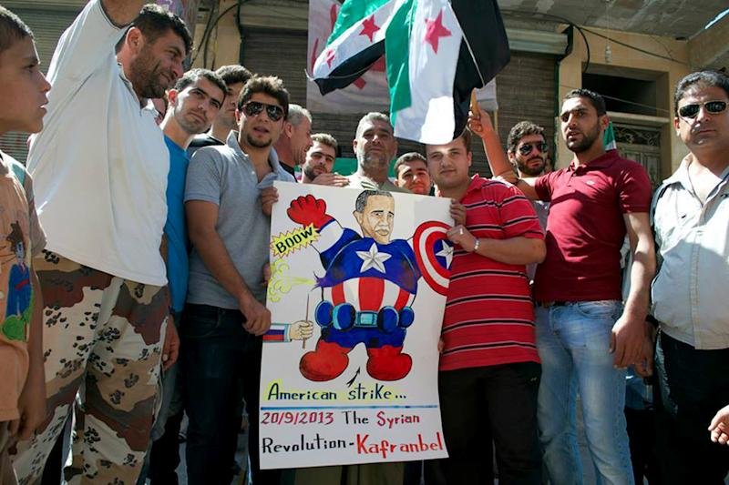 This citizen journalism image provided by Edlib News Network, ENN, which has been authenticated based on its contents and other AP reporting, show anti-Syrian regime protesters hold a poster depicting U.S. President Barack Obama, during a demonstration, in Kafr Nabil town, Idlib province, northern Syria, Friday, Sept. 20, 2013. Syria's main Western-backed opposition group on Friday slammed al-Qaida-linked gunmen and their expanding influence in the country, saying the jihadis' push to establish an Islamic state undermines the rebels' struggle for a free Syria. (AP Photo/Edlib News Network ENN)