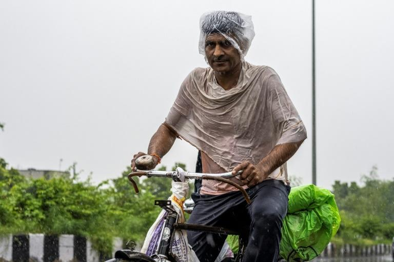 A man rides a bicycle along a street during heavy rain in New Delhi (AFP/Jewel SAMAD)