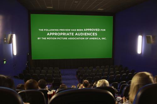 A moviegoing audience watches trailers