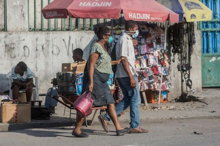 Two people in the Haitian capital Port-au-Prince wear face masks while shopping; a first coronavirus victim has died in Haiti, the government said on April 5, 2020 (AFP Photo/Pierre Michel Jean)
