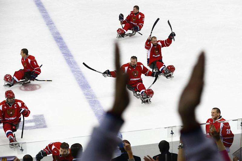 Russia players celebrate after winning the ice sledge hockey semifinal match against Norway during the 2014 Winter Paralympics in Sochi, Russia, Thursday March 13, 2014. Russia won 4-0. (AP Photo/Pavel Golovkin)